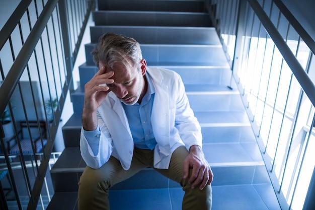 Trauriger arzt, der auf treppe sitzt