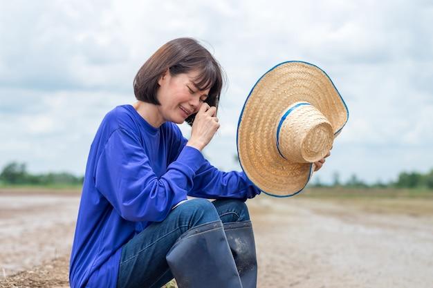 Trauriger asiatischer bauer, der an reisfarm sitzt und weint