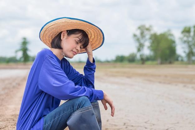 Trauriger asiatischer bauer, der auf einer reisfarm sitzt und sich sorgen macht
