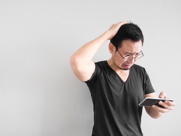 Trauriger asiatischer mann verlor das spiel, das er im smartphone spielte.