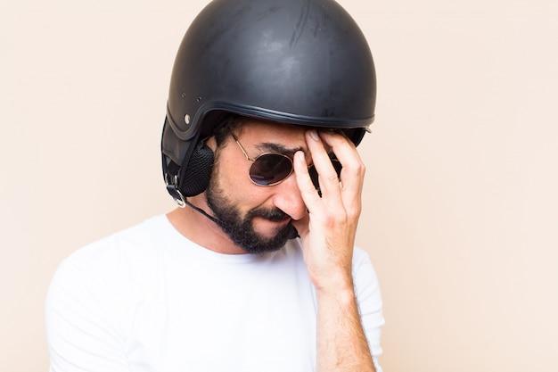 Trauriger ausdruck des jungen kühlen bärtigen mannes mit einem helm