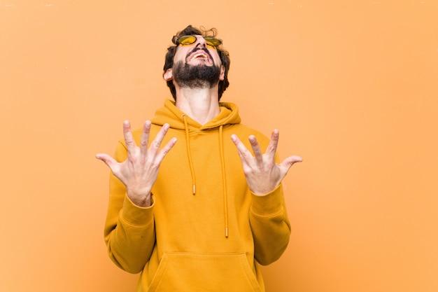 Trauriger ausdruck des jungen verrückten kühlen mannes gegen orange wand