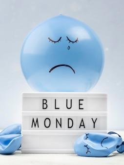 Trauriger ballon mit leuchtkasten für blauen montag