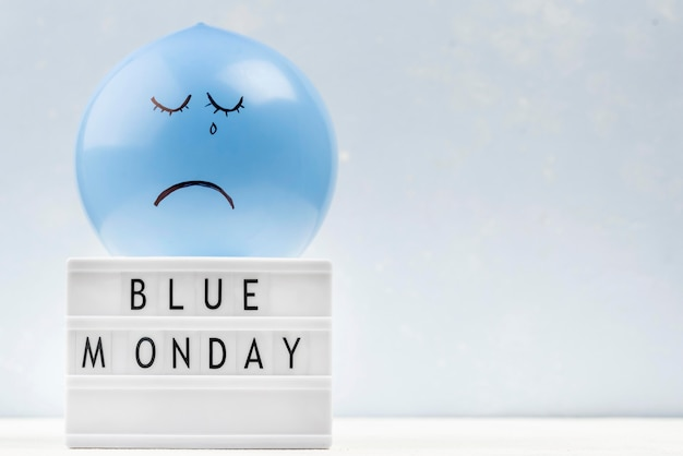 Trauriger ballon mit leuchtkasten und kopierraum für blauen montag