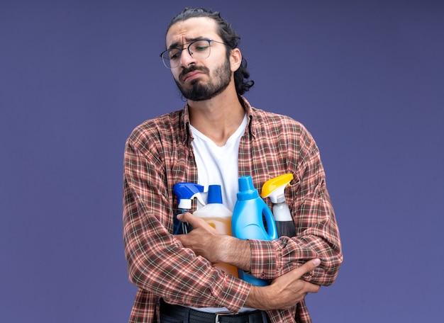 Trauriger blick auf den jungen, gutaussehenden putzmann mit t-shirt, der reinigungswerkzeuge isoliert auf blauer wand hält