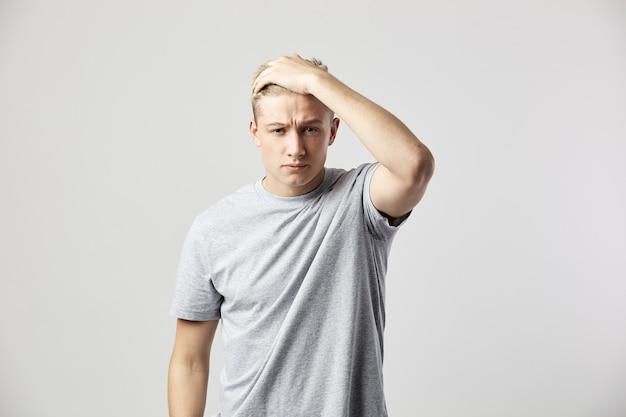 Trauriger blonder kerl in einem weißen t-shirt hält seine hand auf seinem kopf