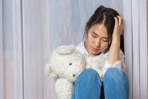 Trauriger brünetter teenager, der teddybär zu hause hält