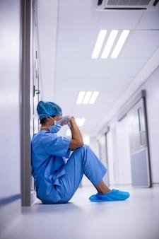 Trauriger chirurg, der auf boden im korridor sitzt