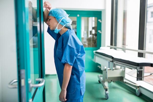 Trauriger chirurg, der sich gegen die glastür lehnt