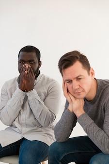 Trauriger denkender und afroamerikanischer mann, der sein gesicht bedeckt