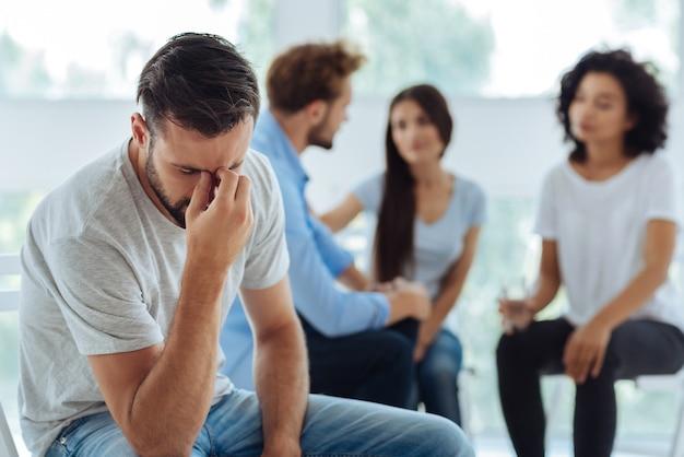 Trauriger depressiver junger mann, der seinen kopf gesenkt hält und die bemerkenswerte brücke berührt, während er nach einer lösung eines problems sucht
