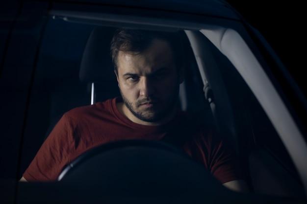 Trauriger depressiver mann, der zeit allein am auto verbringt und frustriert über probleme nachdenkt