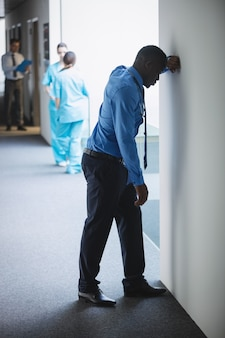 Trauriger doktor an der wand gelehnt