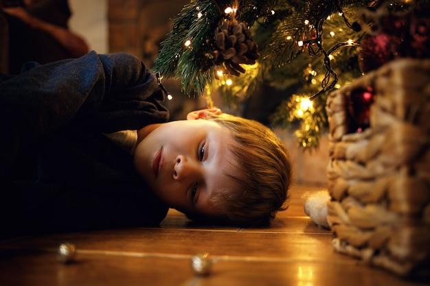 Trauriger einsamer blonder junge 5-7 jahre alt liegt auf dem boden in der nähe des neujahrsbaums