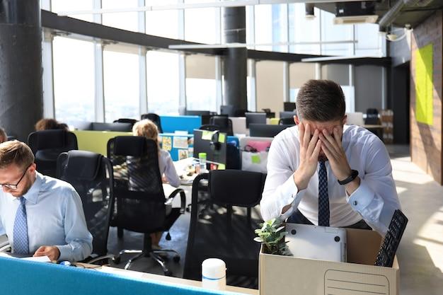 Trauriger entlassener arbeiter nimmt seine büromaterialien aus dem büro mit.