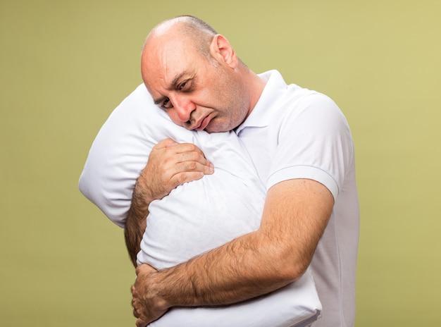 Trauriger erwachsener kranker kaukasischer mann, der kopf auf kissen isoliert auf olivgrüner wand mit kopienraum hält und aufsetzt