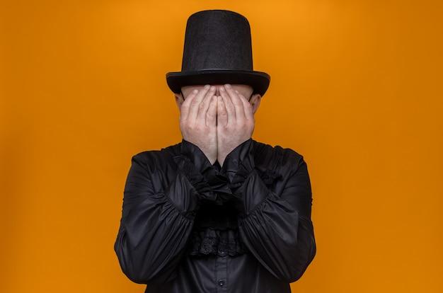 Trauriger erwachsener slawischer mann mit hut und optischer brille in schwarzem gothic-hemd, der sein gesicht mit den händen bedeckt