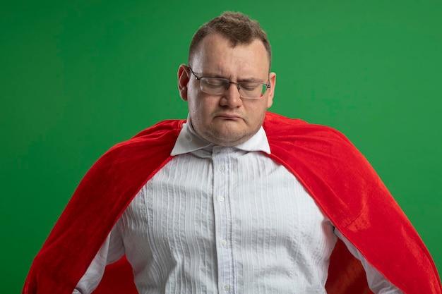 Trauriger erwachsener slawischer superheldenmann im roten umhang, der die brille trägt, die unten auf grüner wand schaut