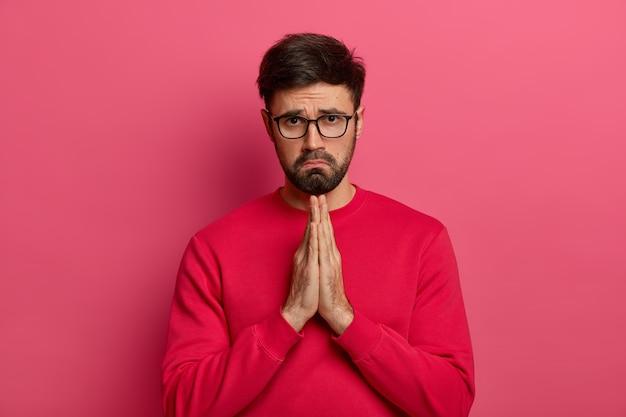 Trauriger flehender mann sagt aufrichtig bitte, macht betende geste