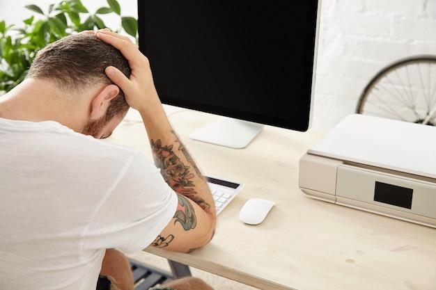 Trauriger freiberufler hat ein hartes projekt und hält seinen kopf in den händen, während er vor seinem funktionierenden computerbildschirm sitzt. seitenansicht
