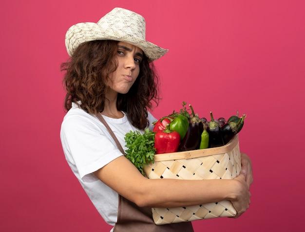 Trauriger gärtner der jungen frau in der uniform, die gartenhut hält, der gemüsekorb lokalisiert auf rosa hält