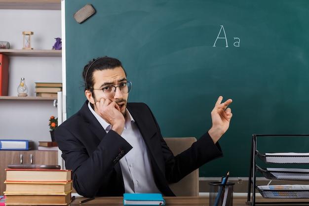 Trauriger gepackter männlicher lehrer mit brille zeigt an der tafel, die am tisch mit schulwerkzeugen im klassenzimmer sitzt