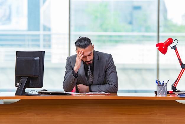 Trauriger geschäftsmann, der im büro sitzt