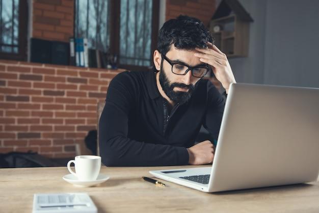 Trauriger geschäftsmann, der im computer im büro arbeitet