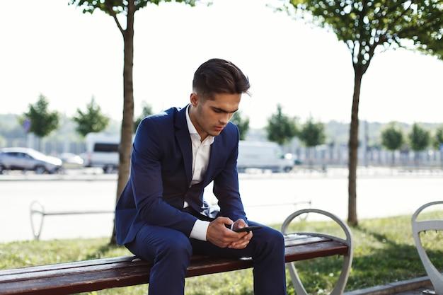 Trauriger geschäftsmann sitzt auf der bank außerhalb der straße
