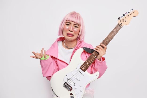 Trauriger gitarrist kann keine neue melodie lernen, sieht unglücklich aus, da rockmusiker verärgert sind, da nicht genug fans trendige kleidung tragen