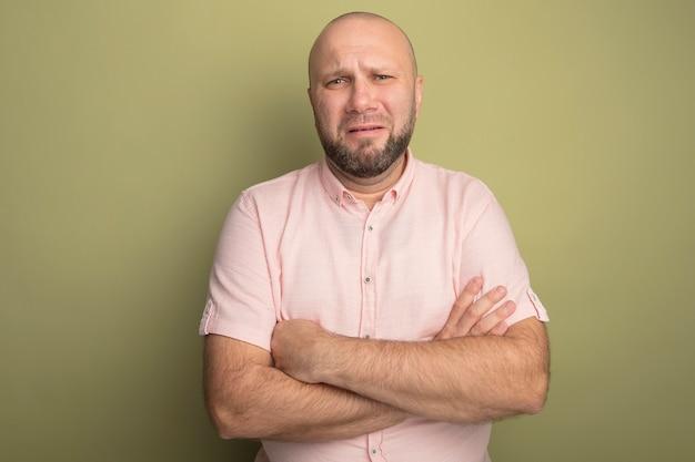 Trauriger glatzkopf mittleren alters, der rosa t-shirt trägt, das hände kreuzt