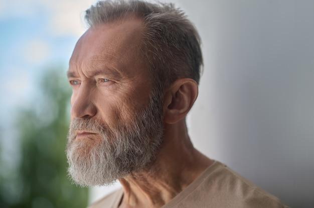 Trauriger grauhaariger kaukasischer mann, der in gedanken versunken ist