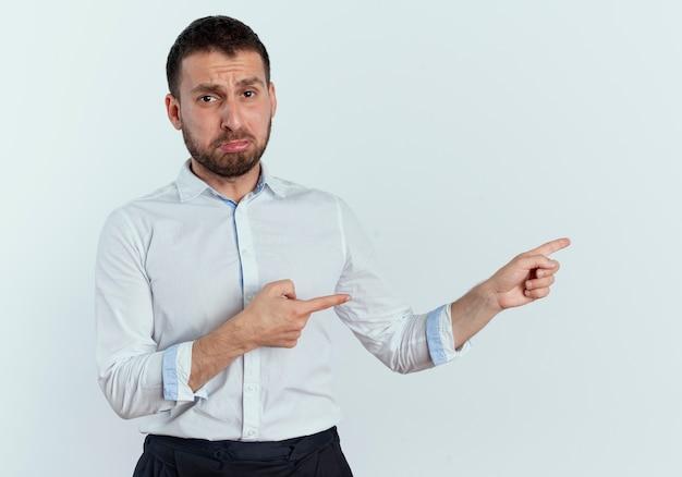 Trauriger gutaussehender mann zeigt zur seite mit zwei händen, die auf weißer wand lokalisiert werden