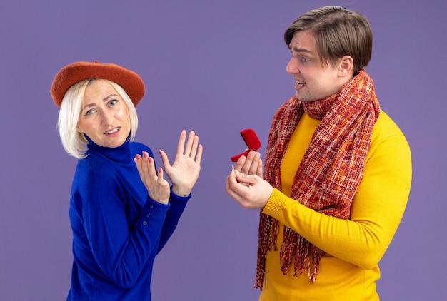 Trauriger gutaussehender slawischer mann mit schal um den hals, der eine rote ringbox hält und eine unzufriedene hübsche blonde frau mit baskenmütze am valentinstag ansieht