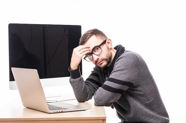 Trauriger hübscher mann in der brille, die auf laptop mit bildschirm des monitors auf seinem rücken arbeitet