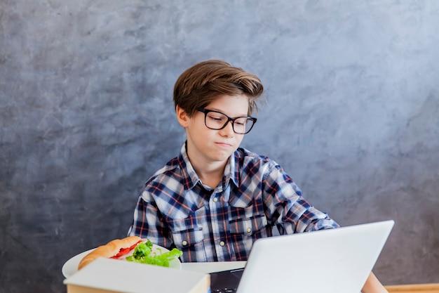 Trauriger jugendlich junge, der laptop benutzt und frühstück hat