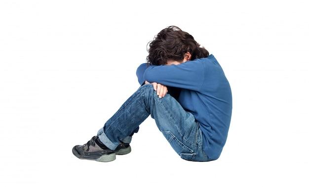 Trauriger junge, der auf dem boden sitzt