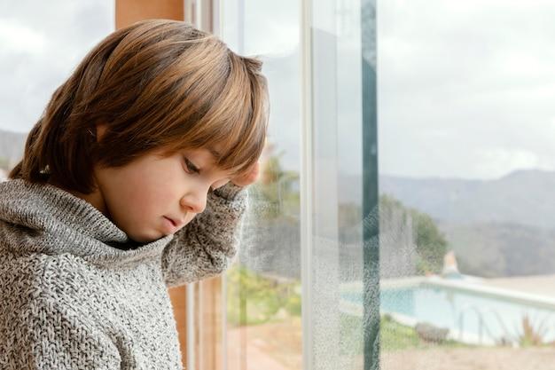 Trauriger junge der seitenansicht, der durch fenster steht