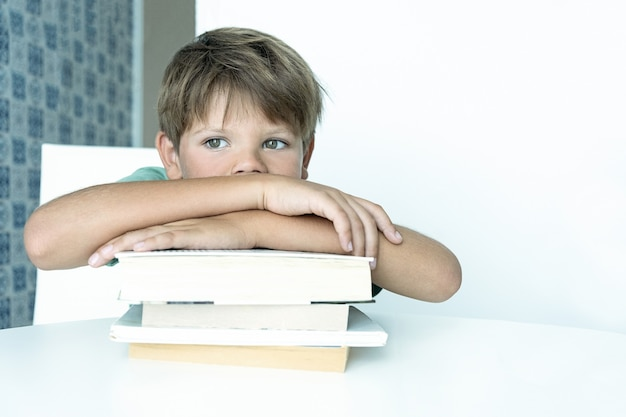 Trauriger junge mit buch macht schulhausaufgaben. zurück zur schule. unglücklicher schüler mit lehrbüchern. fernunterricht.