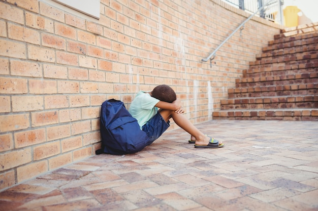 Trauriger junge mit dem kopf auf den knien