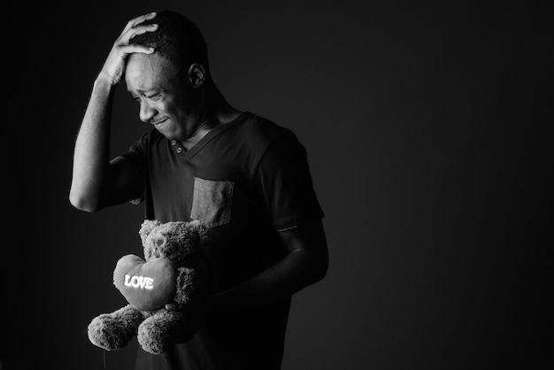 Trauriger junger afrikanischer mann mit teddybär und liebeszeichentext, der kopfschmerzen hat