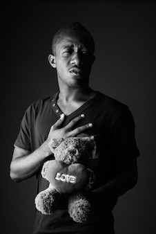 Trauriger junger afrikanischer mann mit teddybär und liebeszeichentext in schwarzweiss