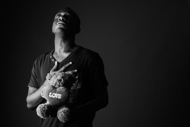 Trauriger junger afrikanischer mann mit teddybär und liebeszeichentextdenken