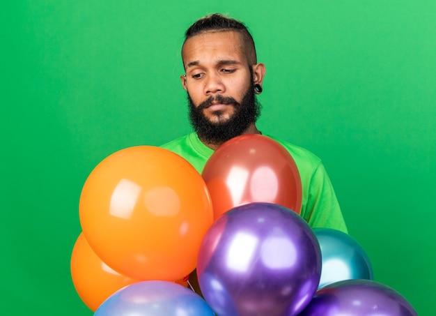 Trauriger junger afroamerikanischer kerl mit grünem t-shirt, der hinter luftballons steht, isoliert auf grüner wand