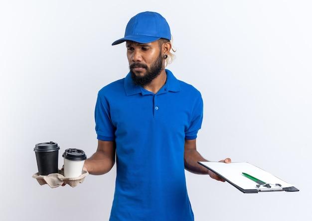 Trauriger junger afroamerikanischer lieferbote, der pappbecher und zwischenablage isoliert auf weißer wand mit kopierraum hält holding