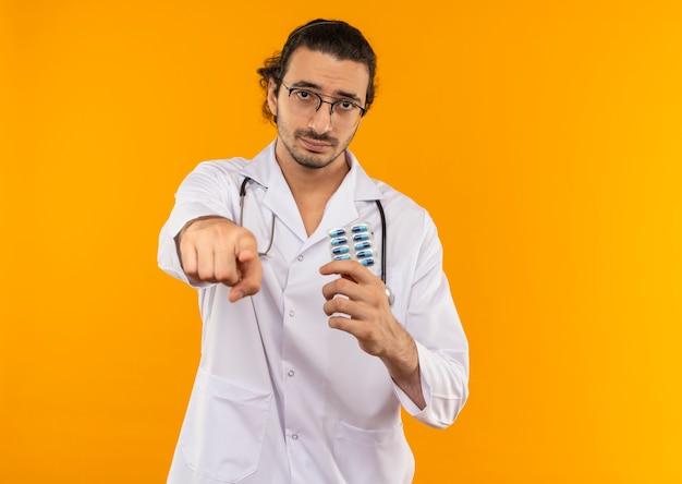Trauriger junger arzt mit medizinischer brille, der ein medizinisches gewand mit stethoskop trägt, das pillen hält und ihnen geste zeigt