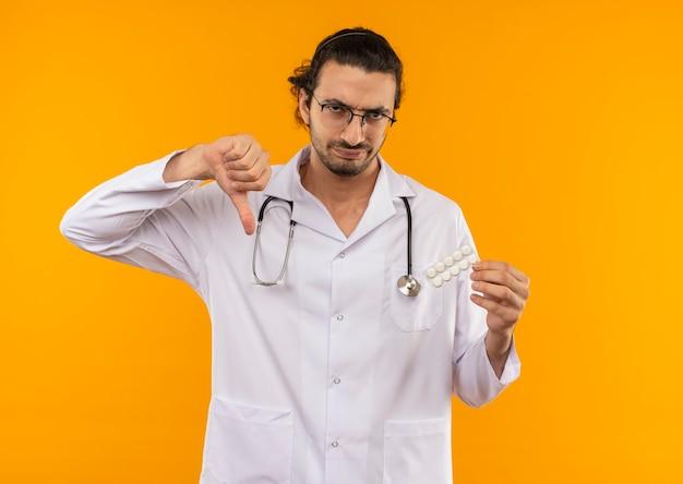 Trauriger junger arzt mit medizinischer brille, die medizinische robe mit stethoskop hält, hält pillen seinen daumen unten auf isolierter gelber wand mit kopienraum