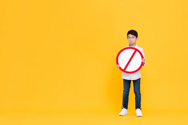 Trauriger junger asiatischer junge, der rote verbotsbeschilderung hält