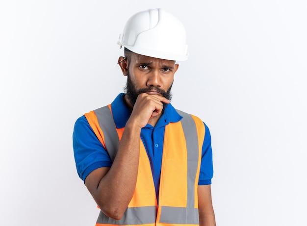 Trauriger junger baumeister in uniform mit schutzhelm, der seine hand auf das kinn legt, isoliert auf weißer wand mit kopierraum