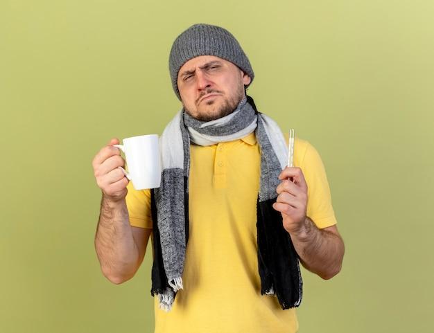 Trauriger junger blonder kranker slawischer mann, der wintermütze und schal trägt tasse hält